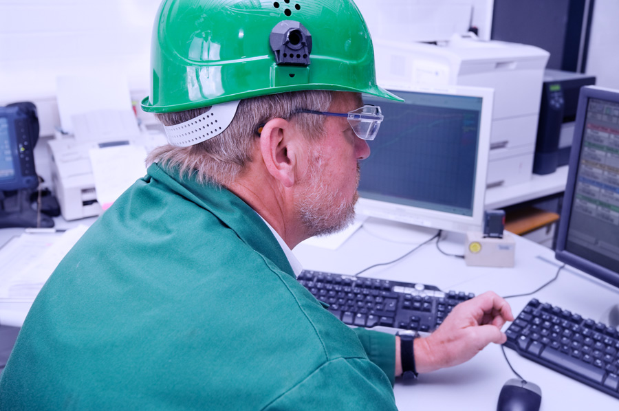 Shutterstock 19756861 Industrial Worker In His Office In Front Of A Pc
